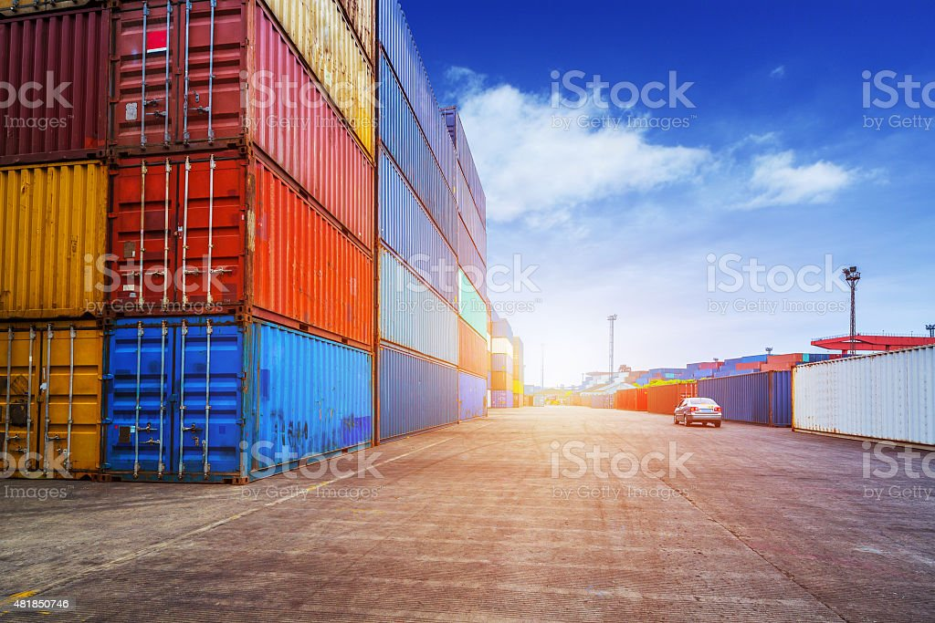 Empty road and containers in harbor at sunset stock photo