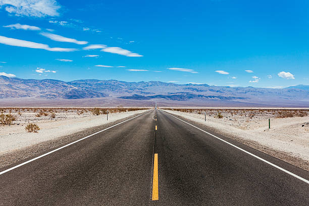 empty road crossing the death valley, california - west direction stock pictures, royalty-free photos & images