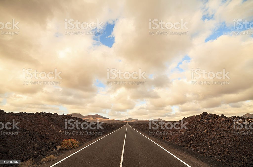 Empty road driving into sunset mountains stock photo