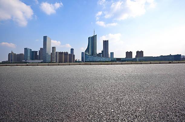 Strada vuota con sfondo città edificio piano - foto stock