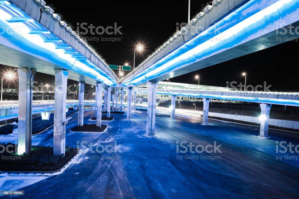 Empty road floor with city overpass viaduct bridge of neon lights night scene Lizenzfreies stock-foto