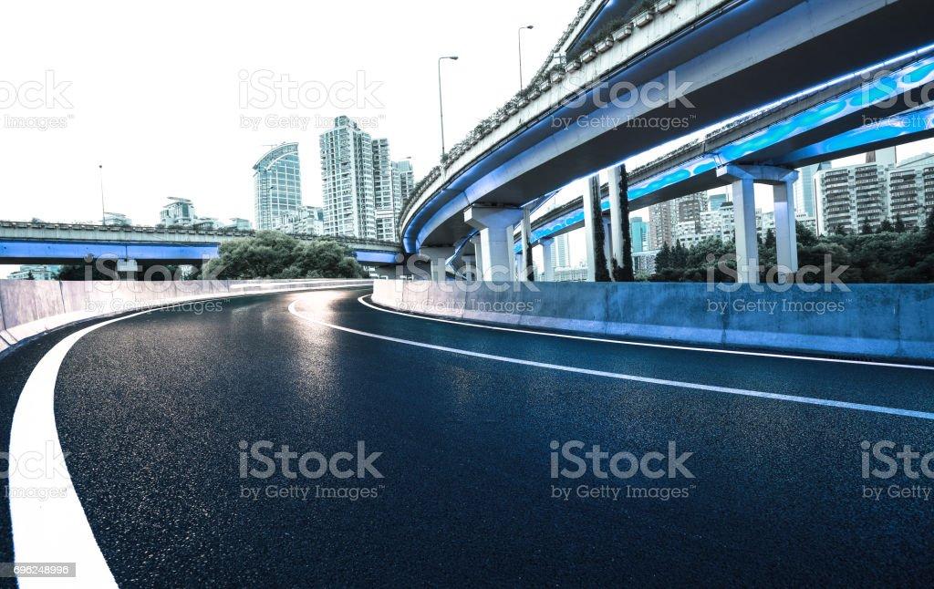 Empty road floor with city overpass viaduct bridge of neon lights night scene stock photo