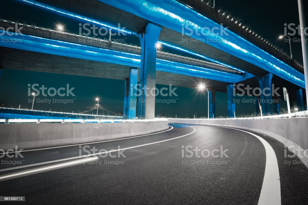 Empty road floor with city viaduct bridge of neon lights night stock photo