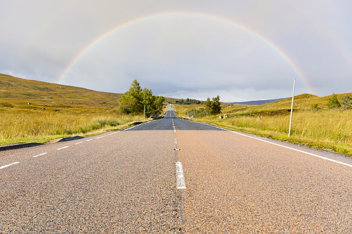 Empty road in the highlands, Scotland, leading to a rainbow - Travel and transportation concept with Scottish landscape on background near Glencoe
