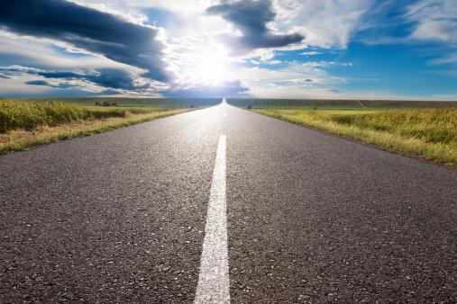 Empty road leading towards the sun