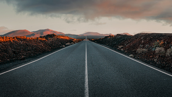 Empty road through the volcanic field at the sunrise with copy space