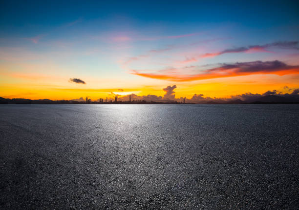 empty road with panoramic cityscape at sunset empty road with panoramic cityscape at sunset asphalt stock pictures, royalty-free photos & images