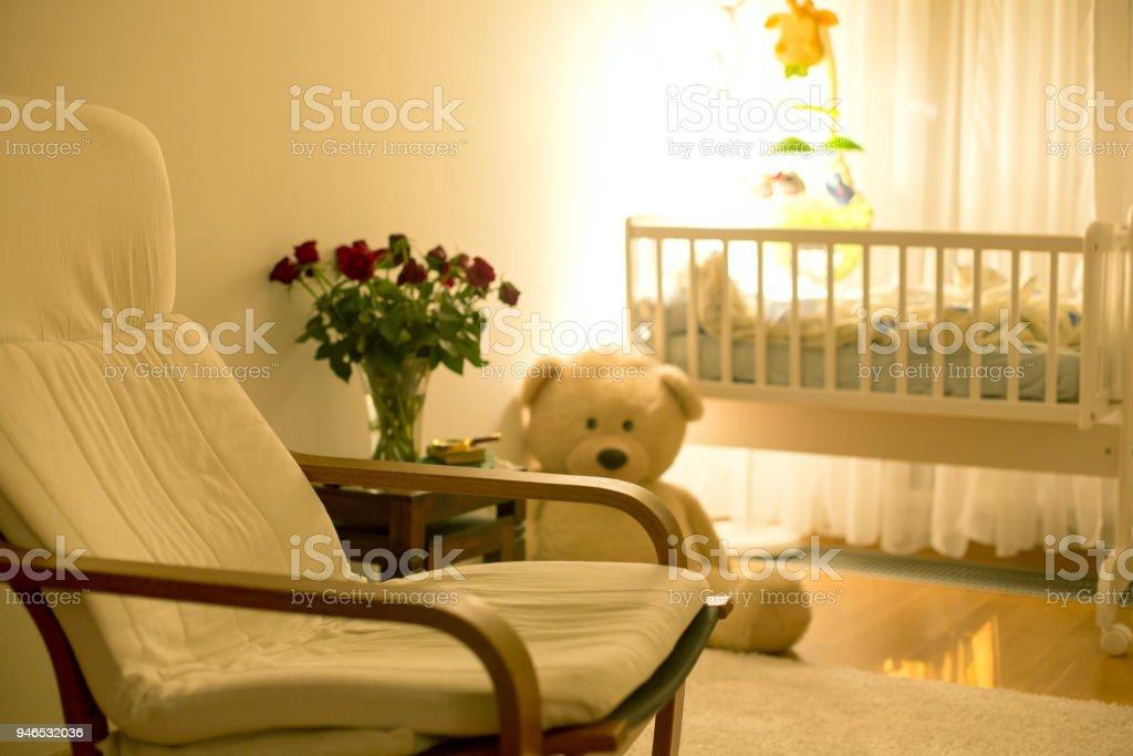Empty rocking chair in a baby boy room with big teddy bear, crib and...