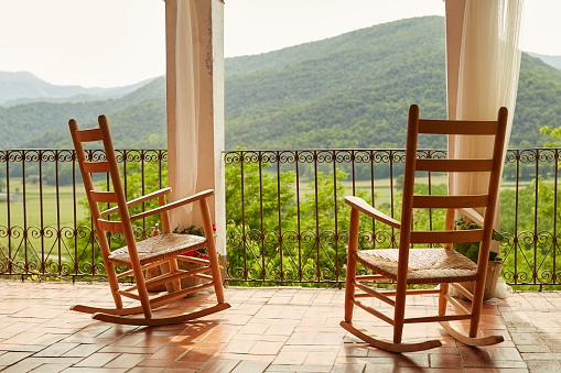Empty Rocking Chairs In Balcony Against Mountains Stock Photo & More