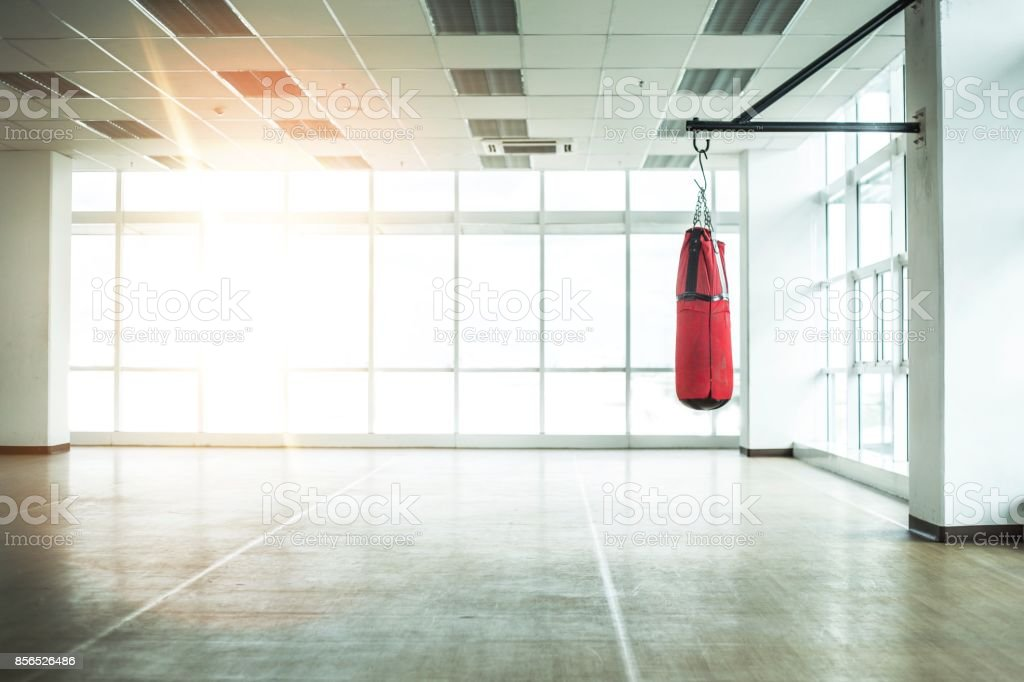 Empty room Gym with Punching bag and Bright sunlight tone background stock photo