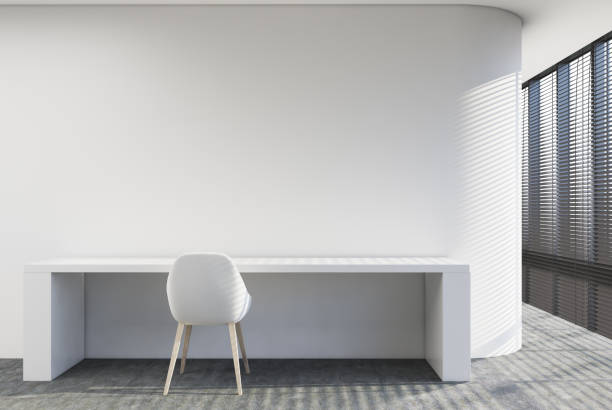 Empty room with a writing table Minimalistic home office with a white writing table and a chair. Loft windows. 3d rendering, mock up empty desk stock pictures, royalty-free photos & images