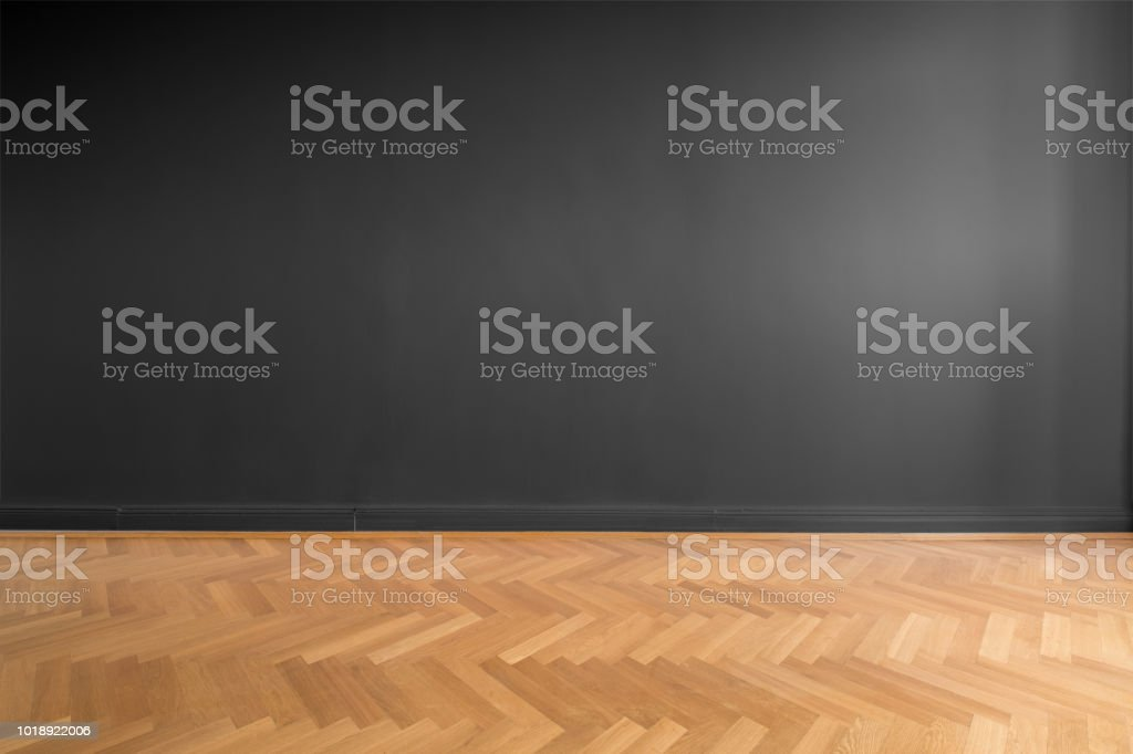 empty room with black wall background and wooden parquet floor stock photo