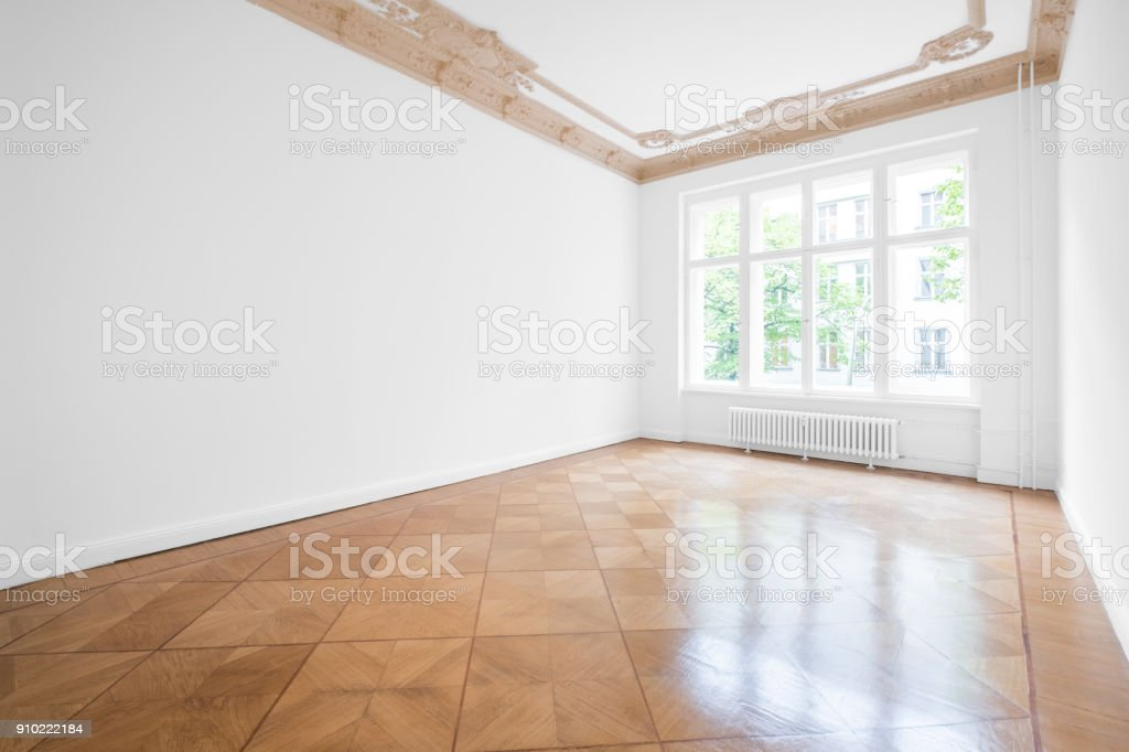 Empty room with parquet floor and stucco ceiling - new renovated flat in old building stock photo