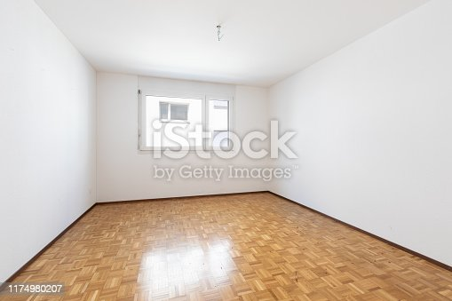 Empty room with vintage parquet. White walls. No one inside