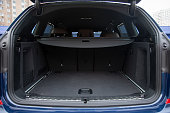 istock empty roomy open trunk of modern crossover car, copy space, Rear view of a car with an open trunk, close up, soft focus, blurred background 1240347235
