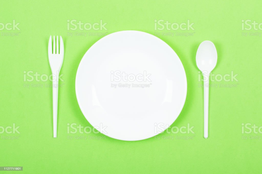 Empty Round White Plate With Spoon Fork On Green Background