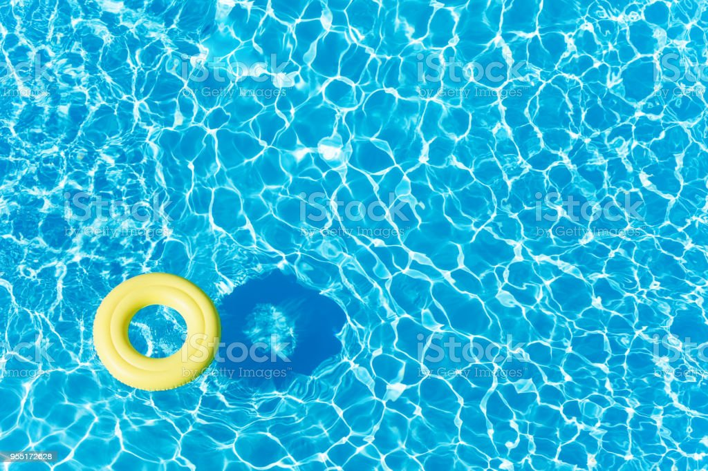 Empty rubber ring floating on blue water surface stock photo