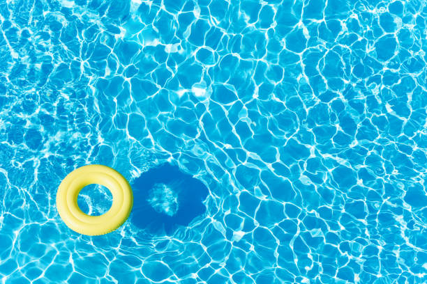 empty rubber ring floating on blue water surface - standing water stock pictures, royalty-free photos & images