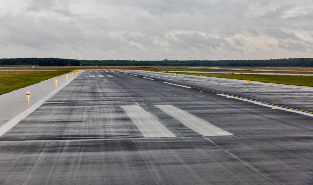 empty runway at the passenger airport in the rain empty runway at the passenger airport in the rain with cloudy airfield stock pictures, royalty-free photos & images
