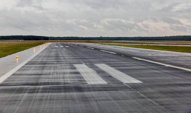 lege start-en landingsbaan op de luchthaven van de passagier in de regen - vliegveld stockfoto's en -beelden
