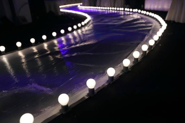 vide piste fashion show avec éclairage incandescent boule le long chemin à pied avec plastique blanc sol dans l'obscurité - défilé de mode photos et images de collection