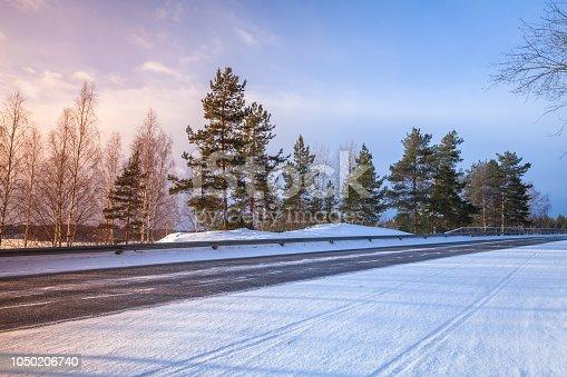 Empty rural asphalt road perspective, winter landscape, Finland