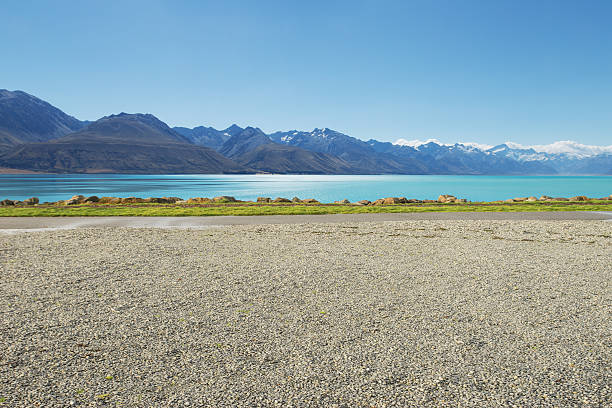 empty rural road near lake and snow mountain - grind stockfoto's en -beelden