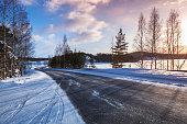 Empty rural road on a lake coast, winter landscape, Finland