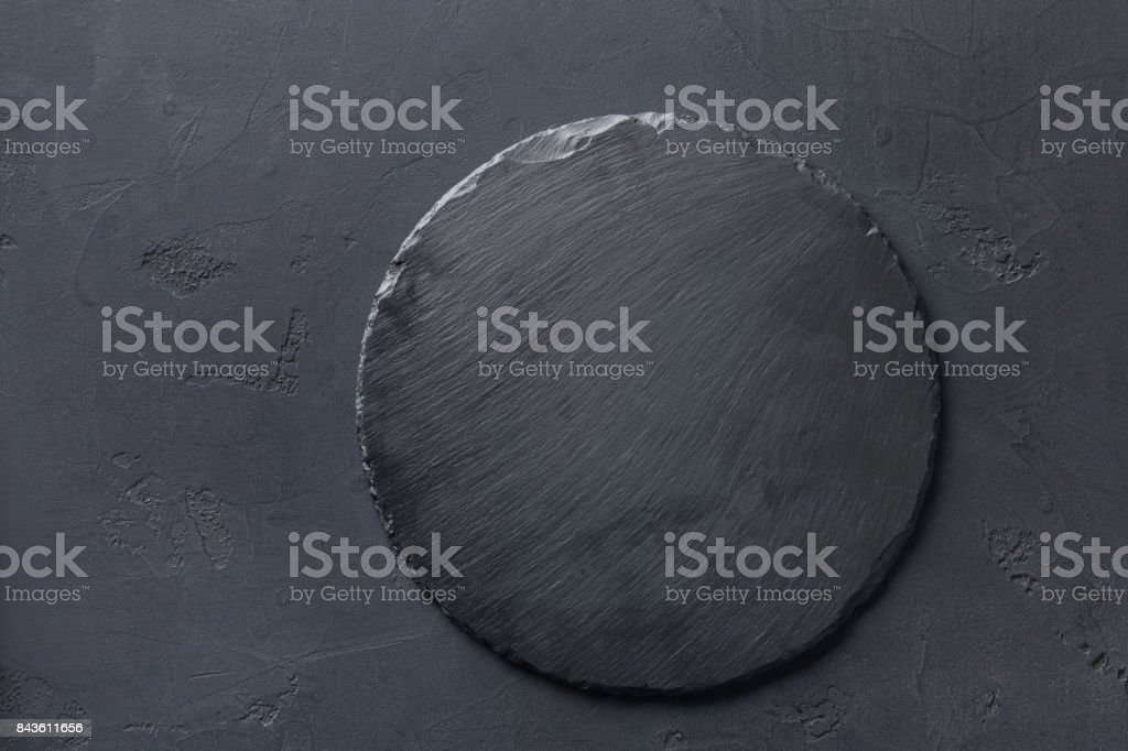 Empty rustic black slate stone plate on dark background stock photo