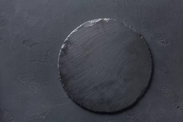 Empty rustic black slate stone plate on dark background stock photo