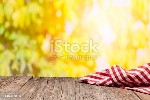 1048926386istockphoto Empty rustic picnic table with gingham cloth against defocused nature background 1146077316