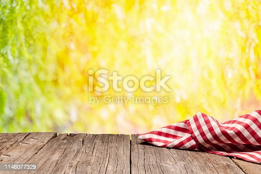 1048926386 istock photo Empty rustic picnic table with gingham cloth against defocused nature background 1146077329