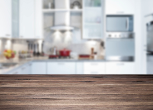 Empty rustic wood kitchen counter-top with blurred modern kitchen at background