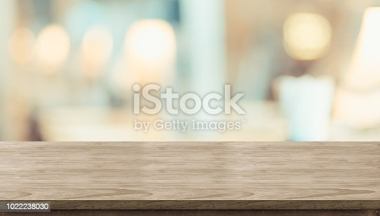 istock Empty rustic wood table and blurred soft light table in restaurant with bokeh background. product display template.Business presentation. 1022238030