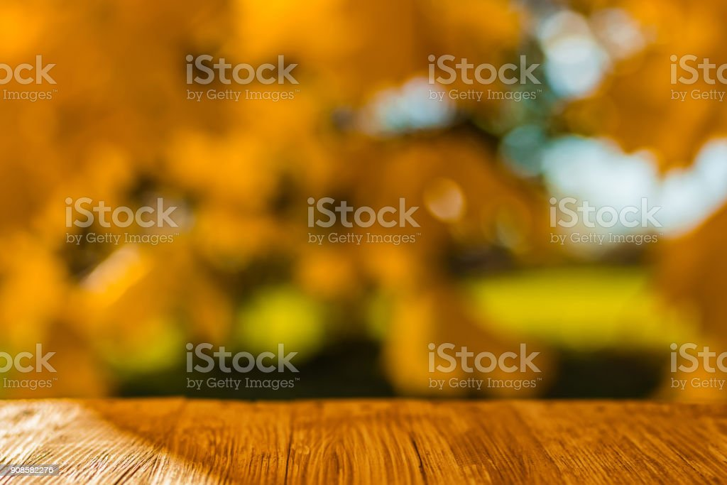 Empty rustic wood table top on blurred colorful autumn leaves background in bright fall forest. Can montage or display your products stock photo