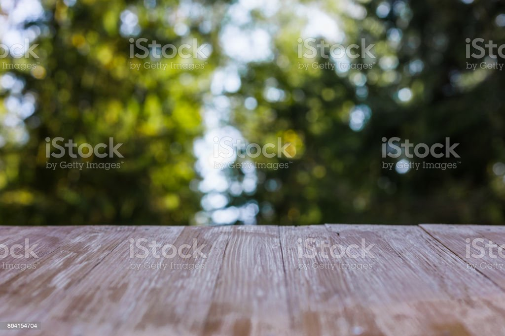 Empty rustic wood table top on blurred forest background at summer. Can montage or display your products royalty-free stock photo
