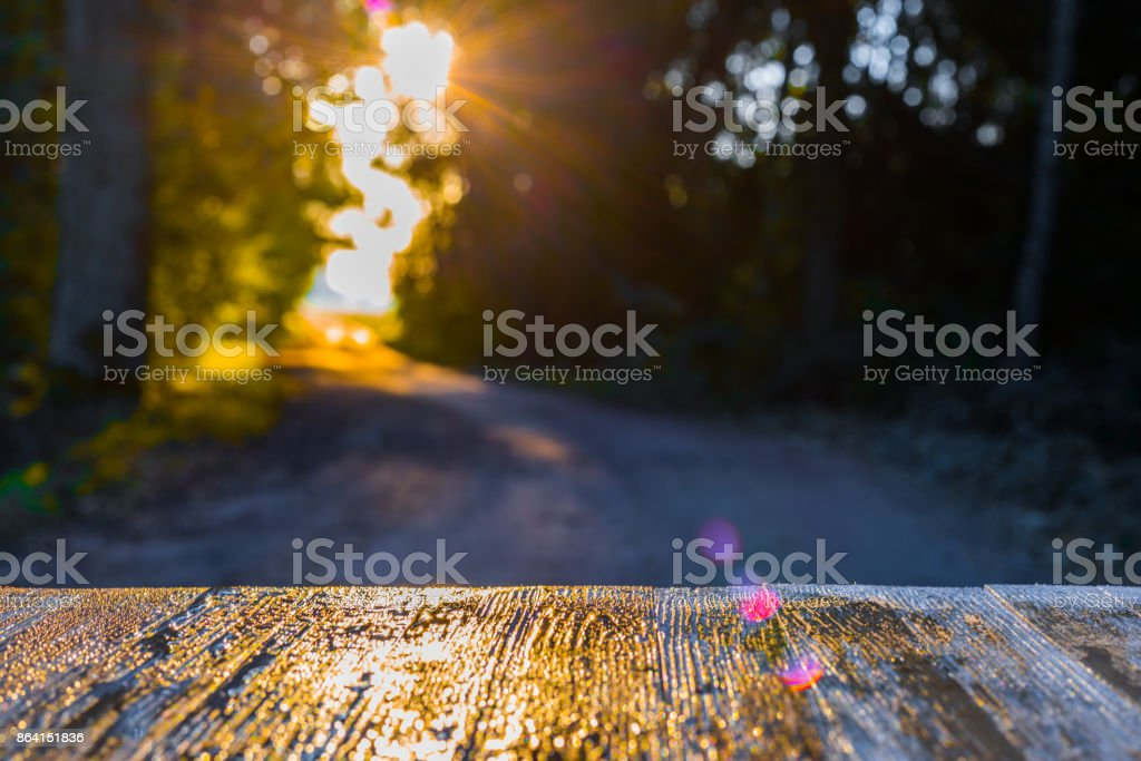Empty rustic wood table top on blurred forest road background on sunrise early autumn morning. Can montage or display your products royalty-free stock photo
