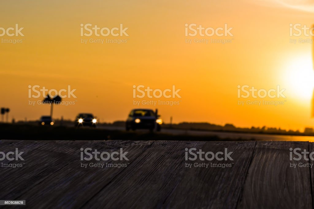 Empty rustic wood table top with motion blurred truck at sunset background. Can montage or display your products stock photo