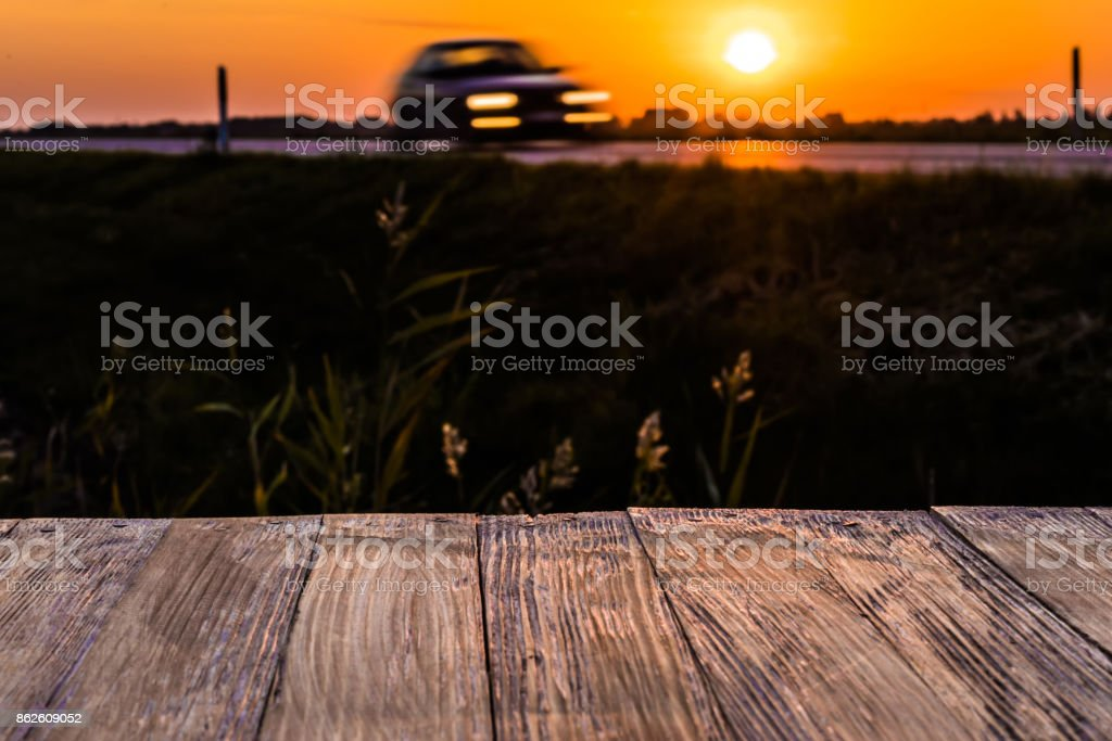 Empty rustic wood table top with motion car at sunset background. Can montage or display your products stock photo