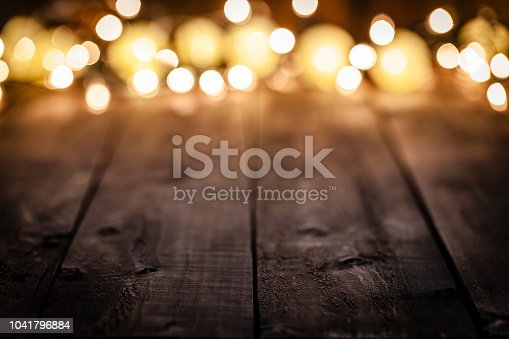 Empty rustic wooden table with defocused Christmas lights at background. Ideal for product display. Predominant colors are brown and yellow. Low key DSRL studio photo taken with Canon EOS 5D Mk II and Canon EF 100mm f/2.8L Macro IS USM.