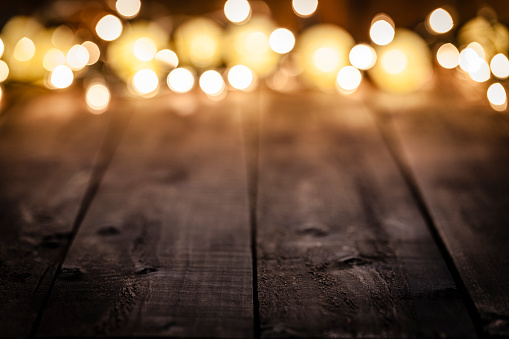 Empty rustic wooden table with blurred Christmas lights at background