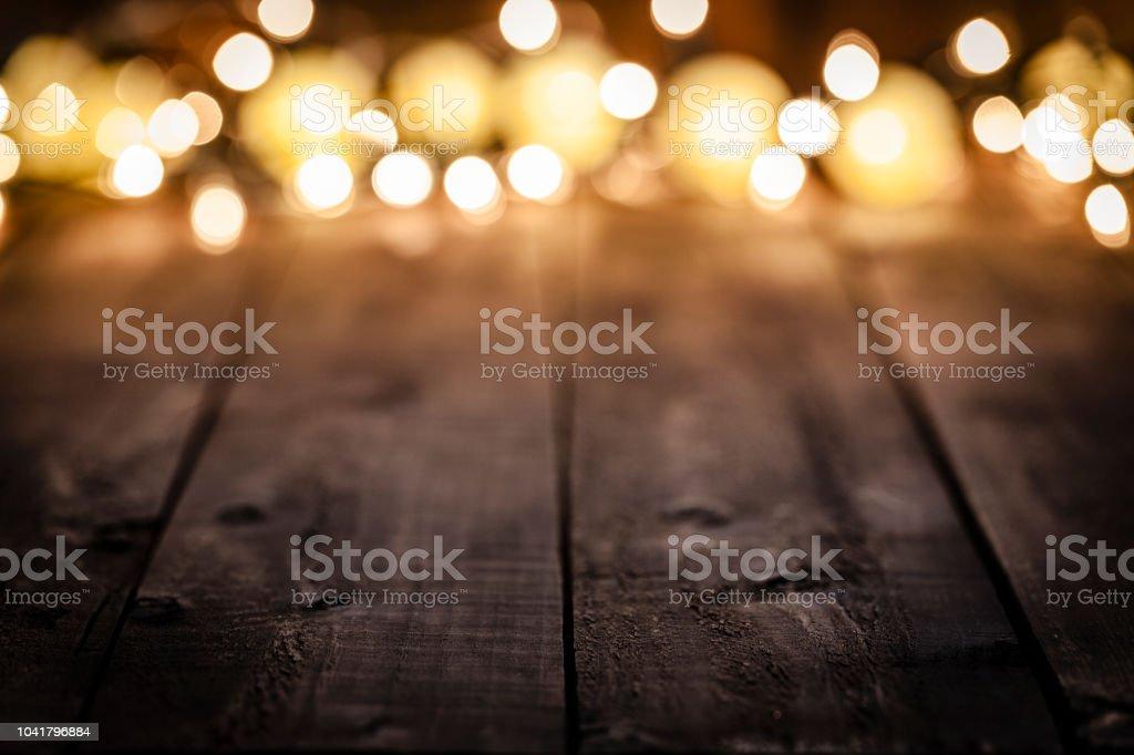 Lege rustieke houten tafel met wazig Kerstverlichting bij achtergrond foto