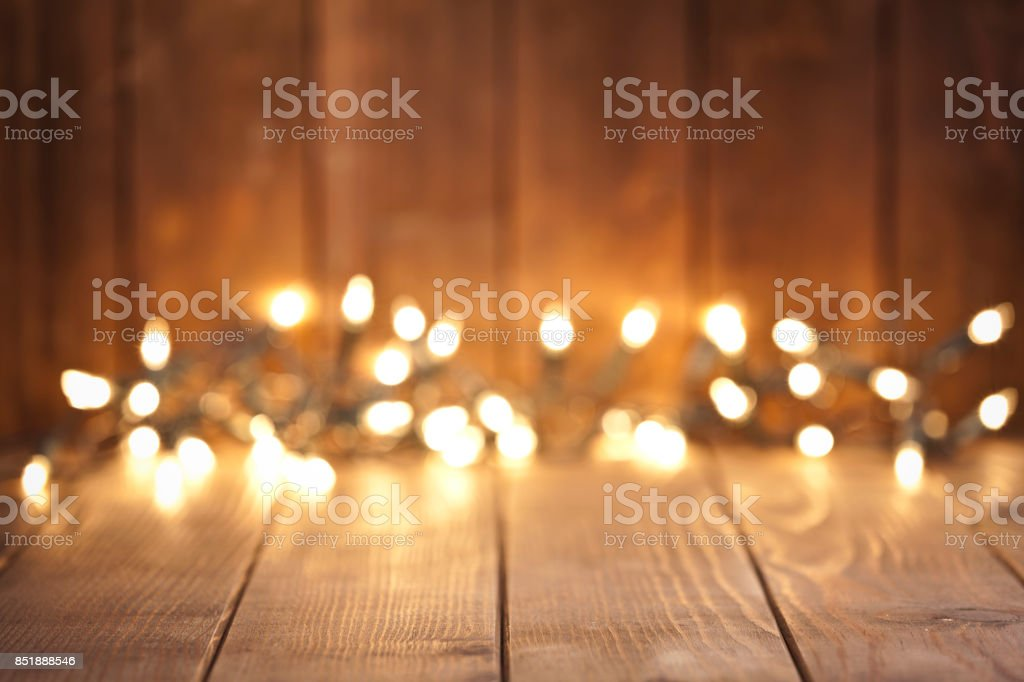 Empty rustic wooden table with blurred Christmas lights at background stock photo