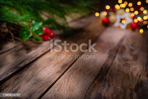 Christmas backgrounds: empty rustic wooden table with defocused Christmas lights at background. Ideal for product display. Predominant colors are brown and yellow. High resolution 42Mp studio digital capture taken with SONY A7rII and Zeiss Batis 40mm F2.0 CF lens