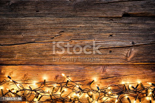 Top view of an empty rustic wooden table with Christmas lights string arranged at the bottom border making a frame and leaving useful copy space for text and/or logo. Predominant colors are brown and yellow. XXXL 42Mp studio photo taken with SONY A7rII and Sony FE 90mm f2.8 Macro G OSS lens
