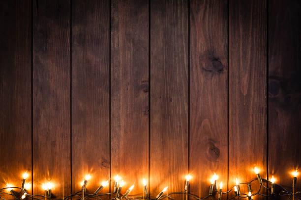 leere rustikalen holztisch mit weihnachten lichter grenze - terrassen lichterketten stock-fotos und bilder