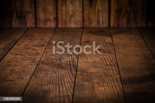 High angle view of an empty wooden plank background with copy space and with a defocused vertical wooden table at the top of the image. Predominant color is brown. Low key DSLR photo taken with Canon EOS 6D Mark II and Canon EF 100 mm f/ 2.8