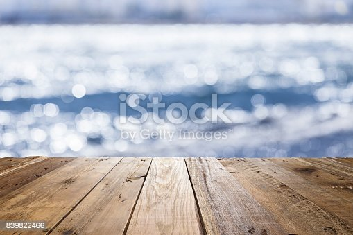 Empty rustic wooden table with defocused shiny sea water at background. Ideal for display products on the table. Copy space available for text and/or logo on background. Predominant colors are blue, white and brown. Composite photo taken with Canon EOS 5D Mk II and Canon EF lenses