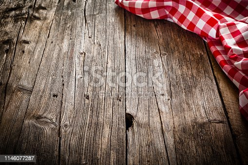 Backgrounds: high angle view of an empty rustic wooden table with vertical stripes. A crumpled red and white gingham tablecloth is at the top right corner of an horizontal frame leaving a useful copy space for text, logo or product montage. Predominant colors are brown and red. Low key DSRL indoors photo taken with Canon EOS 5D Mk II and Canon EF 24-105mm f/4L IS USM Wide Angle Zoom Lens