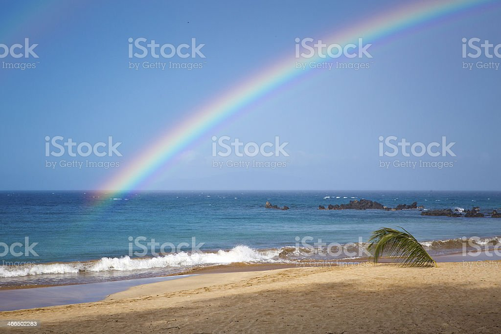 Empty sandy beach with rainbow arch. stock photo